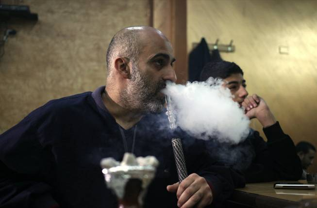 In this Thursday, Jan. 23, 2014, photo, a customer smokes a water pipe at a coffee shop in Amman, Jordan. The kingdom's government  wants to enforce a Western-style smoking ban in restaurants, cafes and other public places.