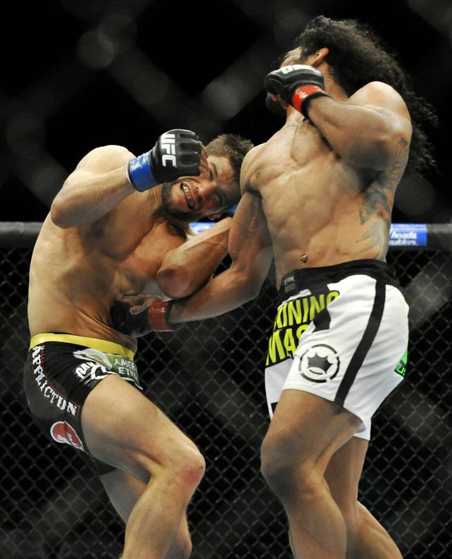Benson Henderson, right, punches Josh Thomson during the main event of a UFC mixed martial arts match in Chicago on Saturday, Jan. 25, 2014.