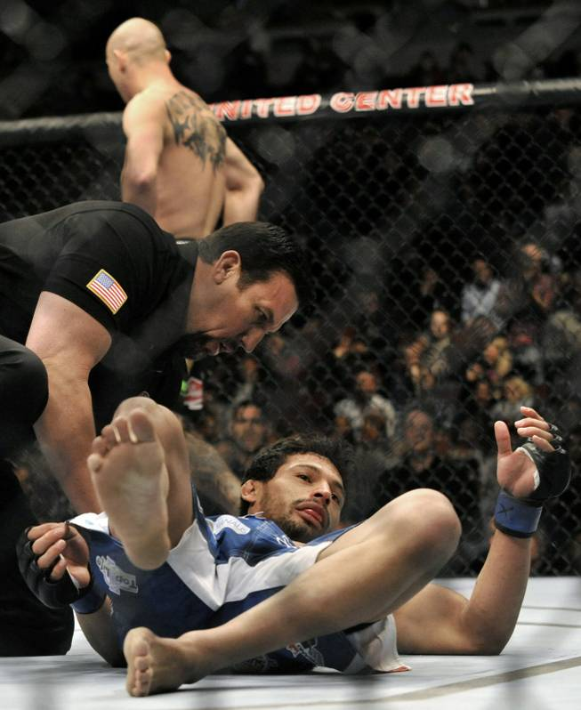 Adriano Martins lays on the canvas after being knocked out by Donald Cerrone during the lightweight bout of an UFC mixed martial arts match in Chicago, Saturday, Jan., 25, 2014.