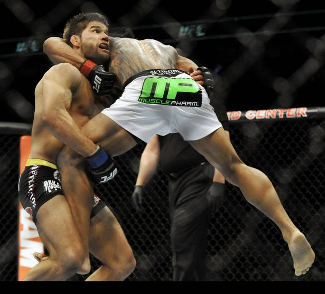 Josh Thomson, left, fights Benson Henderson during the main event of the UFC mixed martial arts event in Chicago, Saturday, Jan., 25, 2014.
