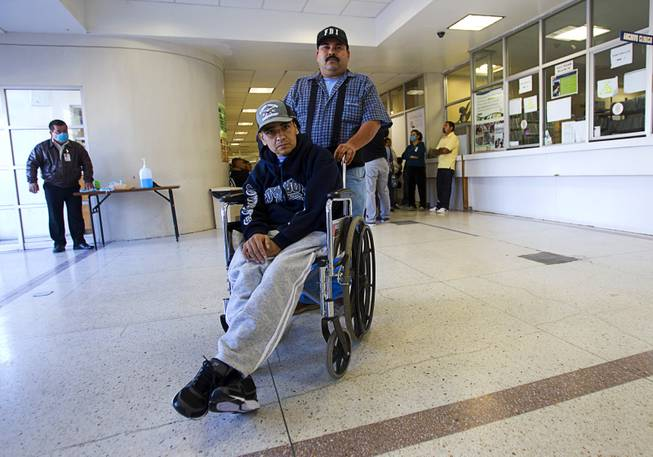 Assistant Jose Alberto Ramirez poses with Francisco Diaz of Las Vegas after a doctor's appointment in the general hospital in Mexicali, Mexico Sunday, Jan. 26, 2014. Diaz was born in Mexico but grew up in Las Vegas with a green card. Diaz was beaten and robbed after he was deported to Mexicali.