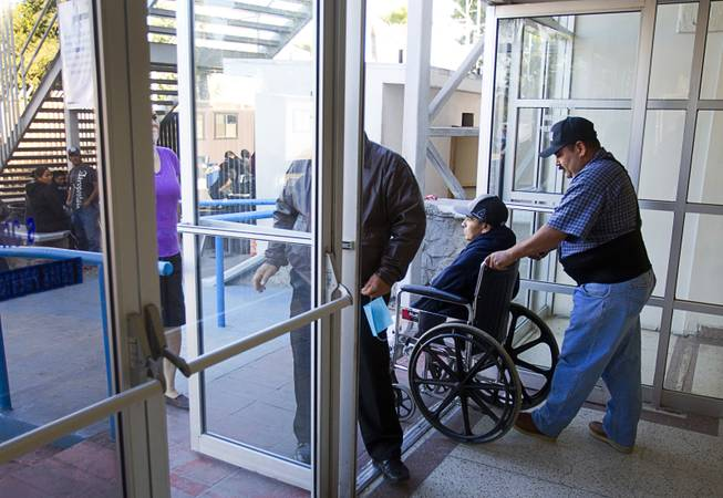 Assistant Jose Alberto Ramirez and Francisco Diaz of Las Vegas leave the general hospital after a doctor's appointment in Mexicali, Mexico Sunday, Jan. 26, 2014. Diaz was born in Mexico but grew up in Las Vegas with a green card. Diaz was beaten and robbed after he was deported to Mexicali.