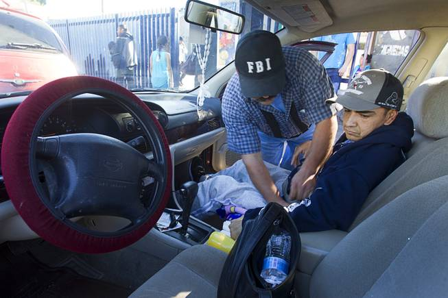 Assistant Jose Alberto Ramirez helps Francisco Diaz with a seatbelt as they leave the general hospital after a doctor's appointment in Mexicali, Mexico Sunday, Jan. 26, 2014. Diaz was born in Mexico but grew up in Las Vegas with a green card. Diaz was beaten and robbed after he was deported to Mexicali.