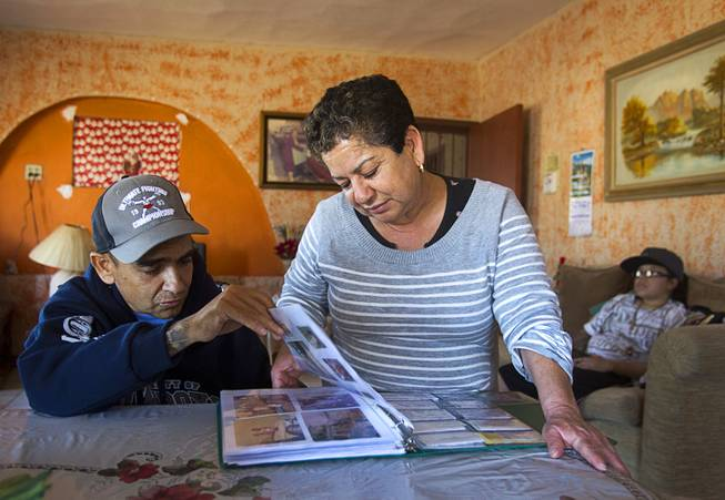 Francisco Diaz looks over a photo album with his mother Adela Espana in Mexicali, Mexico Sunday, Jan. 26, 2014. Diaz was born in Mexico but grew up in Las Vegas with a green card. Diaz was beaten and robbed after he was deported to Mexicali.