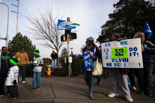High above the crowd and perched on a crosswalk sign, Kristian Martinez, 22, rallied with thousands of diehard 12thMan fans on South 188th Street to see off the Seahawks team buses on their way to the airport en route to New York for Super Bowl XLVIII, Sunday, Jan. 26, 2014, in SeaTac, Wash.