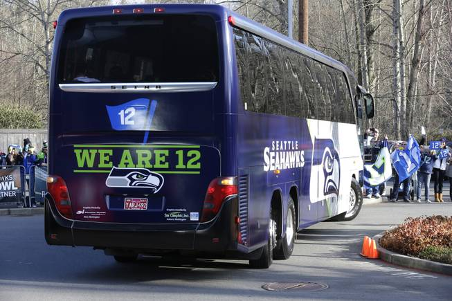 Fans cheer as buses carrying Seattle Seahawks players and coaches leave team headquarters in Renton, Wash., Sunday, Jan. 26, 2014. The team took the buses to the airport for their flight to play the Denver Broncos in the NFL Super Bowl XLVIII football game in East Rutherford, N.J.