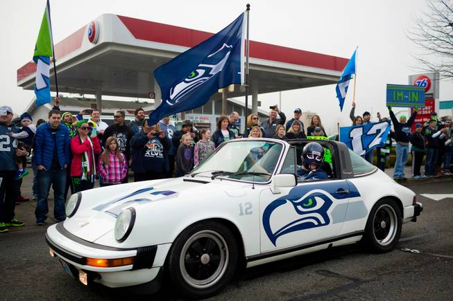 Kel Klink, in his vinyl-wrapped 1978 Porsche 911, rallies alongside thousands of diehard 12thMan fans who lined South 188th Street to see off the Seahawks team buses on their way to the airport en route to New York for Super Bowl XLVIII, Sunday, Jan. 26, 2014, in SeaTac, Wash.