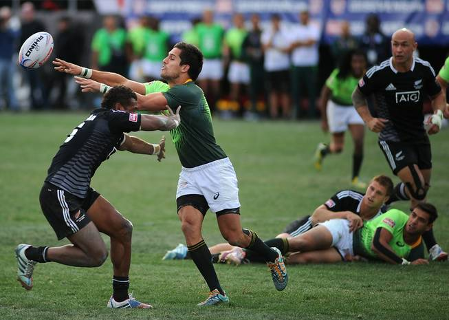 South African Springbok 7's player Stephan Dippenaar, right, passes the ball as he is hit by New Zealand All Blacks 7's Lote Raikabula (left) during the Cup Final match of the USA 7's rugby tournament at Sam Boyd Stadium on Sunday afternoon. South Africa won the match 14-7.