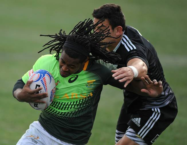 South African player Branco du Preez (left) evades the tackle of New Zealander Bryce Heem (right) on his way to a score during the Cup Final match of the USA 7's rugby tournament at Sam Boyd Stadium on Sunday afternoon. South Africa won the match 14-7.