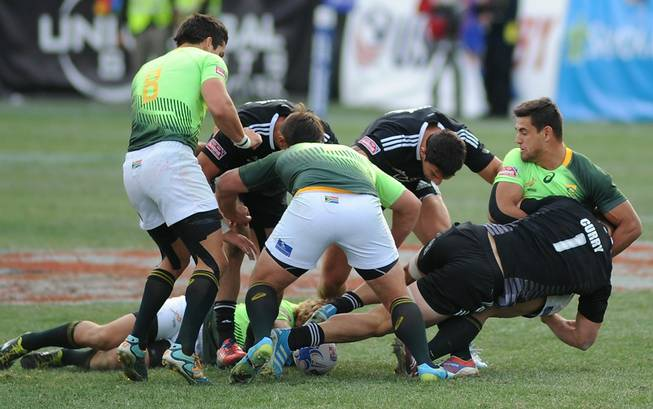 Players battle for control of a loose ball during the Cup Final match of the USA 7's rugby tournament at Sam Boyd Stadium on Sunday afternoon between South Africa and New Zealand. South Africa won the match 14-7.