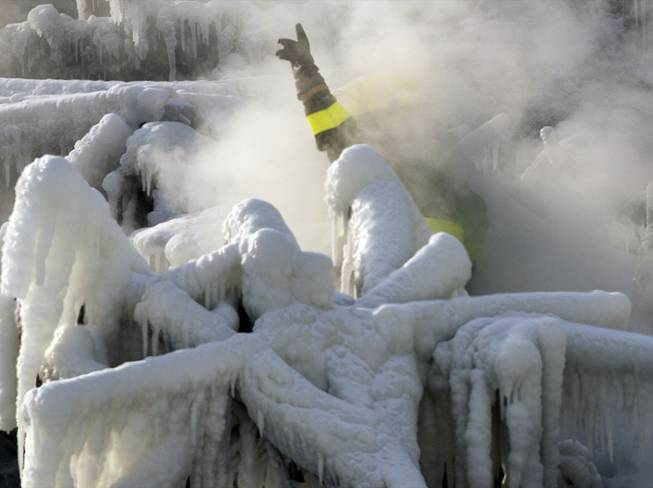 A police investigator, enveloped in steam, signals to colleagues as they search through the icy rubble of a fire that destroyed a seniors' residence Friday, Jan. 24, 2014, in L'Isle-Verte, Quebec.