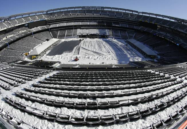 In this photograph taken with a fisheye lens, snow is accumulated on the seats and on the field of MetLife Stadium as crews removed snow ahead of Super Bowl 48 after a snow storm Wednesday, Jan. 22, 2014, in East Rutherford, N.J.