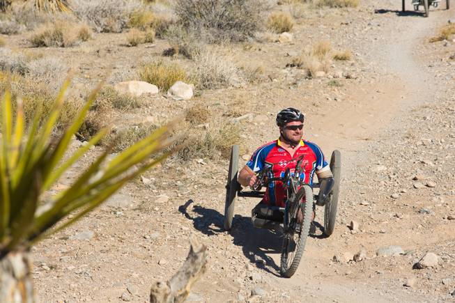 John Masson, a U.S. Army Special Forces Veteran, navigates through Blue Diamond on a 3-wheel hand-powered mountain bike, built by Bill Lasher of Las Vegas, during the Ride 2 Recovery Las Vegas Mountain Bike Challenge Monday, Jan. 27, 2014. Masson, who lost 3 limbs during a roadside bomb attack in Afghanistan in Oct. of 2010, is among many wounded veterans who are being helped by Ride 2 Recovery, a nonprofit organization that provides rehabilitation to injured veterans through cycling.