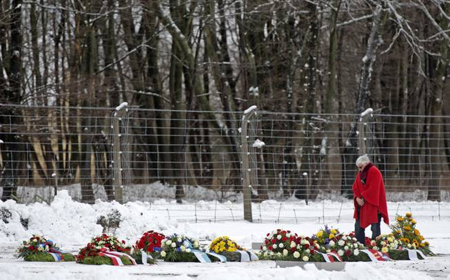 A woman stands between flowers and wreaths during the international Holocaust remembrance day in front of the barbed wire of the former the Nazi concentration camp Buchenwald near Weimar, Germany, Monday, Jan. 27, 2014.