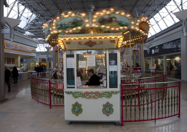 Carousel manager Down Foster waits for customers at The Mall in Columbia after the mall re-opened to the public on Monday Jan. 27, 2014.
