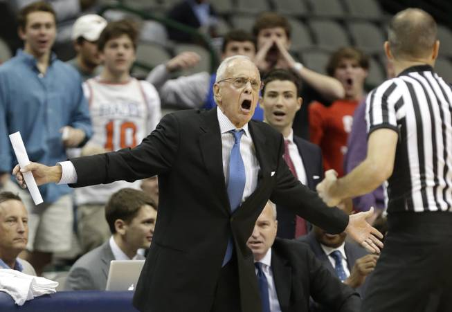 SMU head coach Larry Brown, left, yells at a referee during the first half of an NCAA college basketball game against TCU in Dallas, Friday, Nov. 8, 2013.