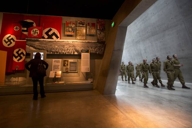 A visitor looks at an exhibit as Israeli soldiers walk at the Yad Vashem Holocaust memorial in Jerusalem, ahead of the International Holocaust Remembrance Day, Sunday, Jan. 26, 2014.