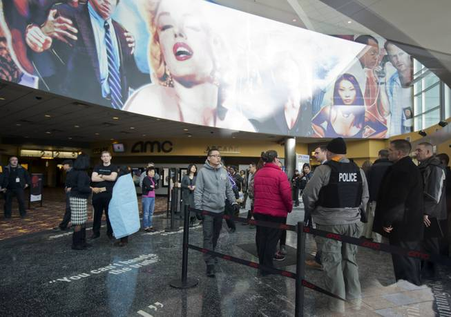 Mall visitors and law enforcement officers are gather at a lobby of a movie theater at The Mall in Columbia Saturday, Jan. 25, 2014, following a shooting in Columbia, Md.  Police say three people died at the mall including the presumed gunman.