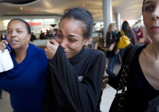 Courtney, center, a friend of one of the victims in Saturday's shooting at the Mall in Columbia, Md,, cries as she walks through the food court with friends after the mall was reopened to the public on Monday Jan. 27, 2014.