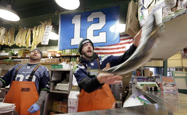 "Fish monger Justin Hall, right, launches a salmon as Scott Smith looks on as the pair wear Seattle Seahawks' jerseys and work beneath a ""12th Man"" flag at the Pike Place Fish Market, Monday, Jan. 27, 2014, in Seattle. Seattle and Denver are both awash in team colors and symbols as Super Bowl Sunday approaches, when the Seahawks play the Denver Broncos in New Jersey for the NFL championship."