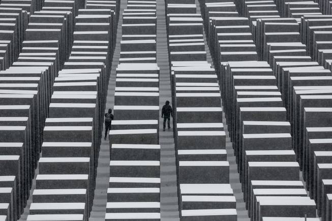 Two visitors walk inside the snow covered Holocaust Memorial at the International Holocaust Remembrance Day in Berlin, Monday, Jan. 27, 2014. The German parliament Bundestag will hold a special remembrance session at the Reichstag building in commemoration of the liberation of the Auschwitz death camp on Jan. 27, 1045.