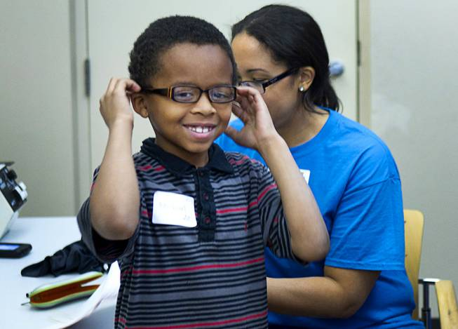 Michael Taylor, 8, a second grader at Duncan Elementary School, tries out eyeglasses at the Andre Agassi College Preparatory Academy Tuesday, Jan. 27, 2014. Over 100 Clark County School District students received free eye exams and new glasses from OneSight. OneSight is an organization providing access to eye care and eyewear to underserved communities.