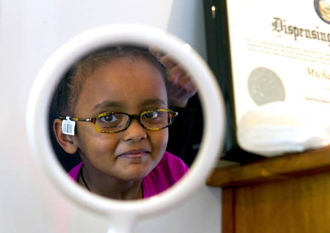 Loza Hailu, 6, a first grader at Hoggard Elementary School, looks in a mirror as she tries out frames in the OneSight mobile vision center at the Andre Agassi College Preparatory Academy Tuesday, Jan. 27, 2014. Over 100 Clark County School District students received free eye exams and new glasses. OneSight is an organization providing access to eye care and eyewear to underserved communities.