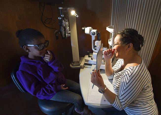 Kindergarden student Tashiani Sewell, 6, looks at a 3D image held by optometrist Erin Frillarte in the OneSight mobile vision center at the Andre Agassi College Preparatory Academy Tuesday, Jan. 27, 2014. Over 100 Clark County School District students received free eye exams and new glasses. OneSight is an organization providing access to eye care and eyewear to underserved communities.