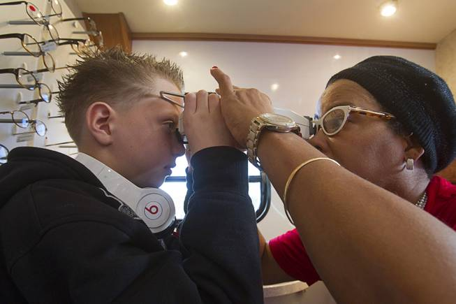 Volunteer Tina Berr, right, takes some measurements on Kevin Stewart, 10, a fifth grader at Deskin Elementary School, in the OneSight mobile vision center at the Andre Agassi College Preparatory Academy Tuesday, Jan. 27, 2014. Over 100 Clark County School District students received free eye exams and new glasses. OneSight is an organization providing access to eye care and eyewear to underserved communities.
