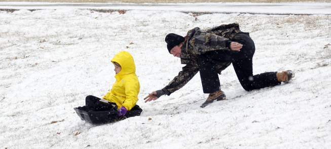 A parent gives his child a push down the hills that surround the soccer fields at Belhaven University in Jackson, Miss., Tuesday, Jan. 28, 2014. An arctic blast spread across Mississippi with below freezing temperatures and treacherous driving conditions.