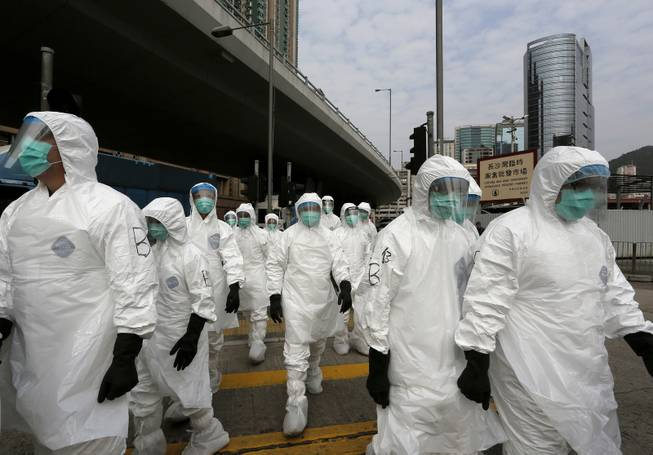 Health workers in full protective gear walk at a wholesale poultry market before culling the poultry in Hong Kong, Tuesday, Jan. 28, 2014.