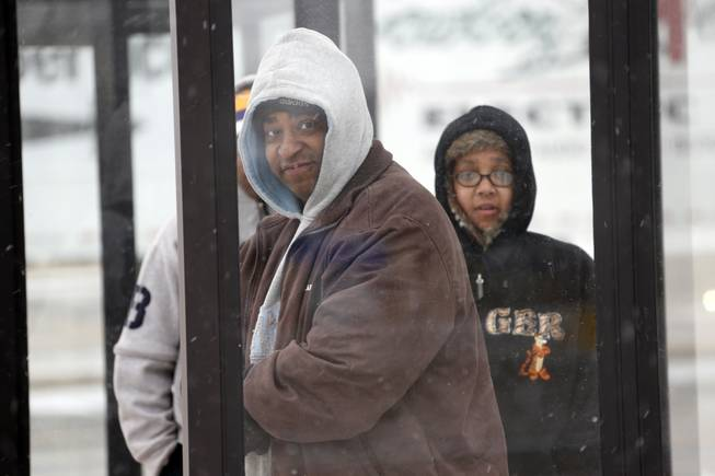 Richard Robinson of Jackson and others wait under a shelter for their morning bus ride into downtown Jackson, Miss., Tuesday, Jan. 28, 2014, as ice and snow flurries have brought on difficult driving conditions. A severe winter storm is expected to hit the state bringing ice and snow to the Gulf Coast. Snow is expected to get heavier though mid-morning before temperatures rise by early afternoon.
