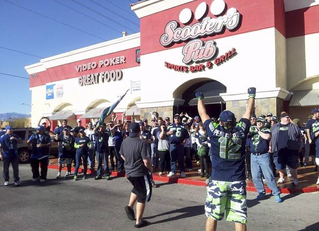 Seahawks fans gather for a photo outside Scooter's Pub during the Seahawks vs. Rams game Sunday, Dec. 29, 2013.
