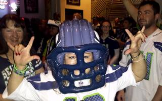 A Seahawks fan poses for the camera during the Seahawks vs. Saints playoff game at Scooter's Pub Jan. 11, 2014.
