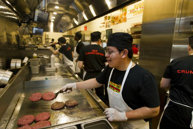 Grill cook Isaac Serpas prepares burgers in the kitchen of chef Bobby Flay's Bobby's Burger Palace on Wednesday, Jan. 29, 2014, on the Strip in Las Vegas.