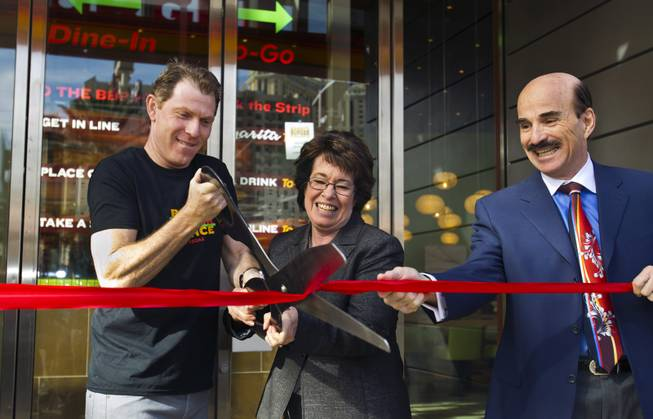 Chef Bobby Flay cuts a ribbon with Clark County Commissioner Mary Beth Scow during the opening ceremony of his Bobby's Burger Palace on Wednesday, Jan. 29, 2014, on the Strip in Las Vegas.