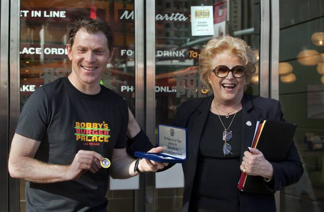Chef Bobby Flay is presented with a Key to the City by Mayor Carolyn Goodman at the ribbon-cutting ceremony of his Bobby's Burger Palace on Wednesday, Jan. 29, 2014, on the Strip in Las Vegas.