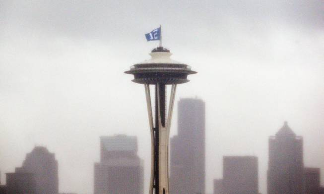 "A ""12th Man"" flag, honoring Seattle Seahawks fans, is barely visible as it flutters atop the Space Needle in the rain Wednesday, Jan. 29, 2014, in Seattle. The Seahawks play the Denver Broncos in Super Bowl XLVIII on Sunday."
