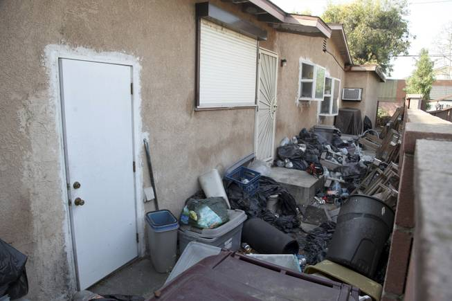 Trash is shown stacked against the home of William Buchman Wednesday Jan. 29, 2014 in Santa Ana, Calif. Buchman has  been arrested for investigation of neglect in the care of animals, after authorities found at least 300 living and dead pythons in plastic bins inside Buchman's stench-filled suburban home.