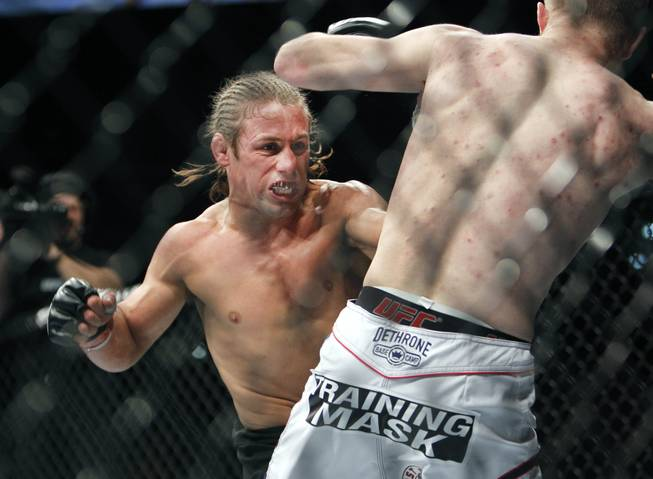 Urijah Faber, left, battles Michael McDonald in a UFC Mixed Martial Arts bantamweight fight in Sacramento, Calif., on Saturday, Dec. 14, 2013.