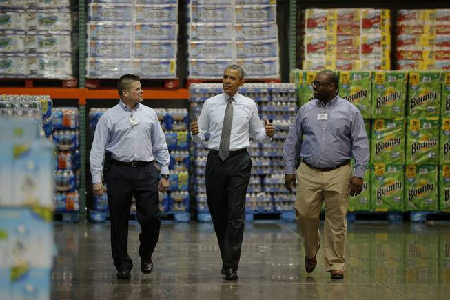 President Barack Obama walks with Ricky Banner, assistant general manager, right, and Emile (Ray) Quevedo, floor employee, at a Costco store in Lanham, Md., Wednesday, Jan. 29, 2014, before he spoke about raising the minimum wage.