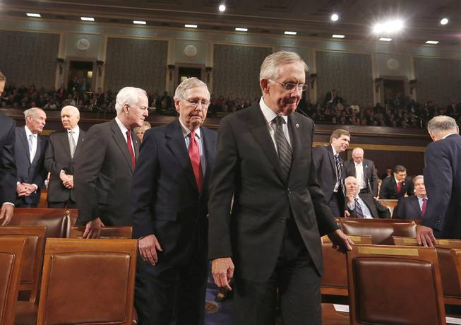 Senate Majority Leader Harry Reid leads Senate Minority Leader Mitch McConnell and Minority Whip John Cornyn to the front of the chamber before President Barack Obama delivers the State of Union address Tuesday, Jan. 28, 2014, before a joint session of Congress.