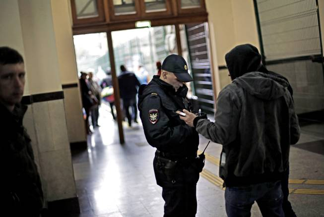 A police officer checks the identification of a passerby in the central train station, Wednesday, Jan. 29, 2014, in Sochi, Russia, home of the upcoming 2014 Winter Olympics.