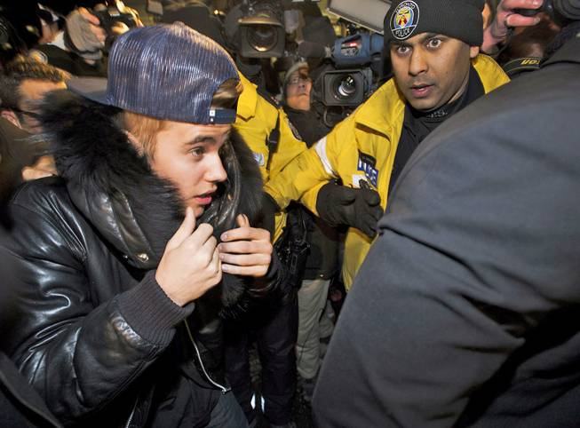 Singer Justin Bieber is swarmed by media and police officers as he turns himself in to city police for an expected assault charge in Toronto on Wednesday, Jan. 29, 2014.