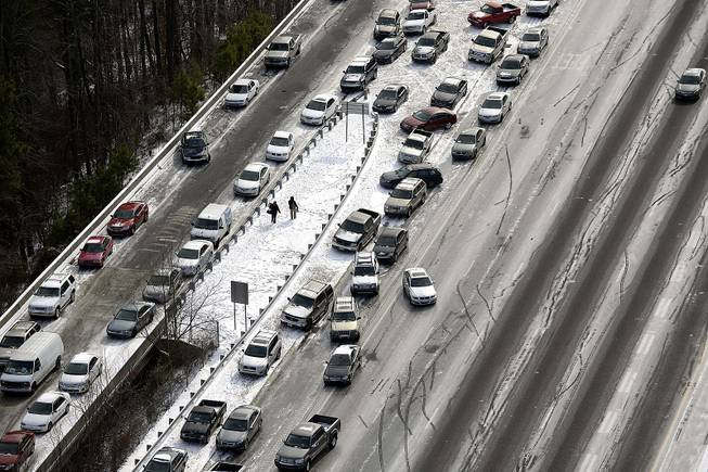In this aerial view looking at I-75 north at Mt. Paran Road, abandoned cars are piled up on the median of the ice-covered interstate after a winter snow storm Wednesday, Jan. 29, 2014, in Atlanta.