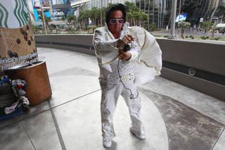 Elvis impersonator Michael Romeo tries to control his cape  in the wind while working on the Strip Thursday, Jan. 30, 2014. Romeo worked on Hollywood Boulevard in Los Angeles for 12 years before moving to the Las Vegas Strip two years ago.