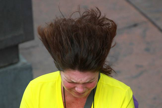 A woman's hair blows in the wind while she walks down the Strip as a weather system moves through the valley Thursday, Jan. 30, 2014.