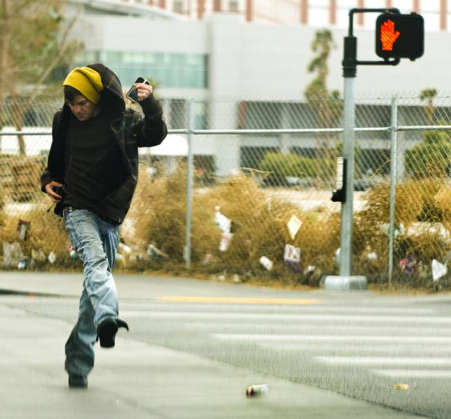 A pedestrian chases a dropped pack of cigarettes blowing away with the high winds along S. Las Vegas Blvd. on Thursday, Jan. 30, 2014.