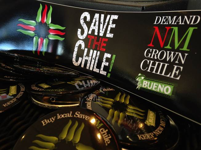 In this July 31, 2013, image, a collection of bumper stickers and buttons promoting New Mexico-grown chile sits on the order counter at Hello Deli restaurant in Albuquerque.