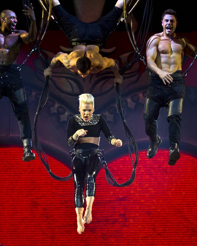 "Pink begins her ""The Truth About Love Tour"" concert hanging from a bungee above the stage Friday, Jan. 31, 2014, at MGM Grand Garden Arena. Lead dancer Colt Prattes is at right."